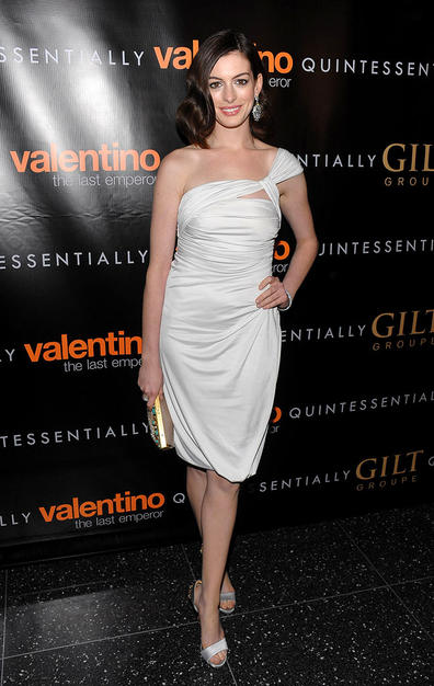 "Anne Hathaway arrived at New York's Museum of Modern Art for the premiere of ""Valentino: The Last Emperor"" in a white asymmetrical ruched dress, courtesy of the famous fashion designer."