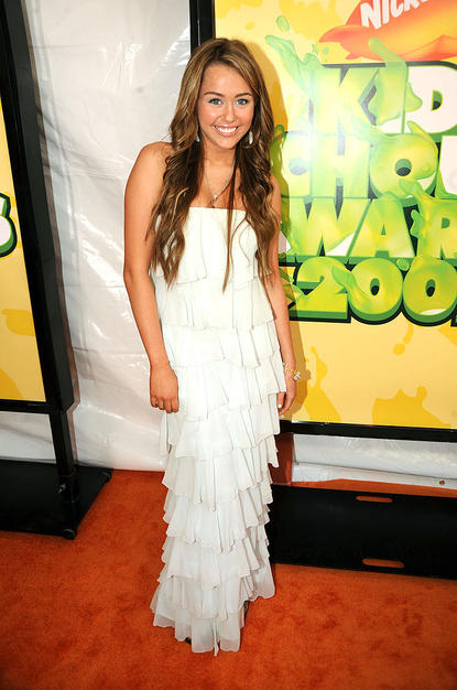 Miley Cyrus glowed in a ruffled white gown thanks to her highlighted hair and bronzed bod.