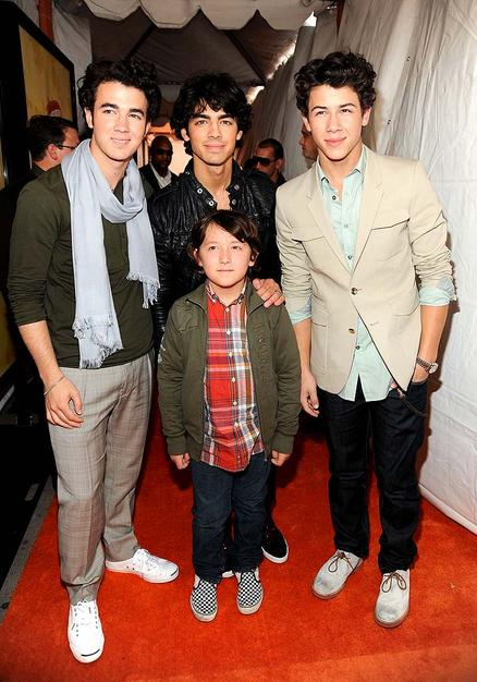 "The Jonas Brothers (Kevin, Joe, and Nick) brought their uniquely different styles to the orange carpet, as well as their youngest sibling, Frankie. Hopefully the adorable ""Bonus Jonas"" won't follow in his big bros' fashion footsteps when it comes to man scarves!"