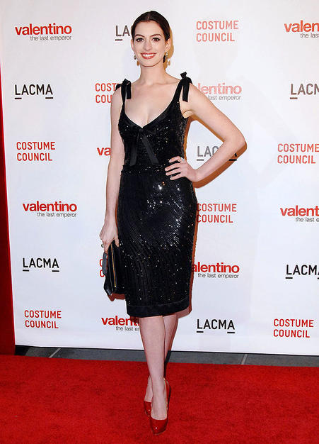 "Anne Hathaway pops a pose in a sequined pencil dress with ribbon accents at the premiere of ""Valentino: The Last Emperor"" at the Los Angeles County Museum of Art."