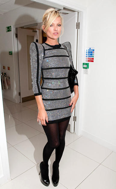 "Supermodel Kate Moss sported a futuristic Balmain frock, complete with structured shoulders and stripes, along with black tights and sky-high YSL ""Trib Two"" heels at a recent fashion fete in London."