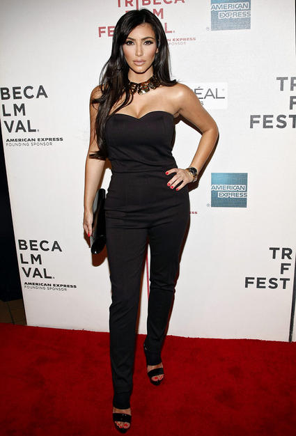 Thankfully, Kim Kardashian ditched her wretched golden weave and rocked the red carpet at the Tribeca Film Fest in a stunning strapless jumpsuit, metallic choker, and bright red nails.