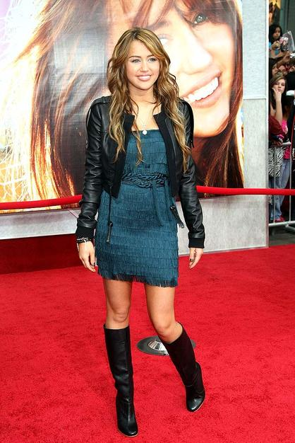 """Miley Cyrus dressed to impress in a modified Alberta Ferretti frock, cropped leather jacket, and black knee-high boots for the premiere of """"Hannah Montana: The Movie."""""""