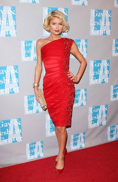 Paris Hilton channeled Marilyn Monroe at a recent charity event in a ravishing red one-shouldered Georges Chakra Couture cocktail frock, matching patent leather pumps, and a styled bob.