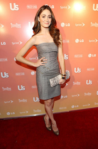 Emmy Rossum looked fabulous in a gray grommet-enhanced wrap dress, chunky jewelry, and bronze heels.